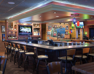 The new Applebee's prototype design includes a sleeker, slightly larger bar area  with strategically placed TV screens, varied seating styles and a dramatically  lit back bar.